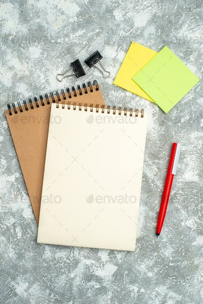 Vertical view of two kraft spiral notebook with pen colorful notepapers on ice background