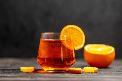 Front view of fresh delicious juice in a glass with orange limes on dark background