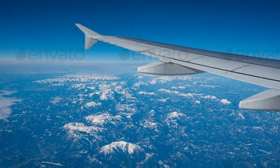 Plane wing in a flight and dramatic cloudscape white clouds over europe