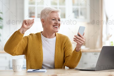 Excited grandmother holding smartphone and raising fist up