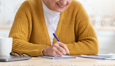 Cropped of old woman sitting in kitchen, taking notes
