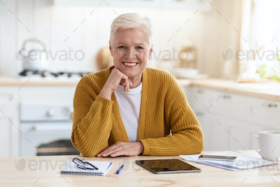 Happy senior woman freelancer working from home