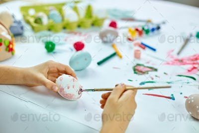 Unrecognizable little girl painting, drawing with brush eggs at home