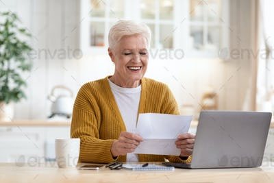 Positive grandmother sitting in kitchen, reading letter