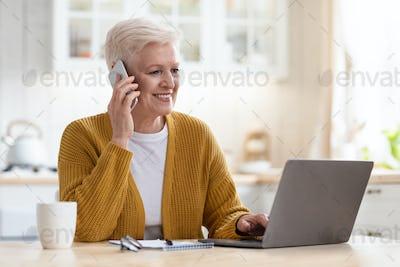 Smiling senior woman having conversation on phone, working on laptop