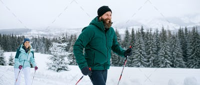 Mature couple cross country skiing outdoors in winter nature, Tatra mountains Slovakia.