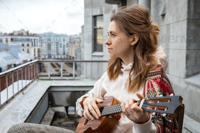 Young hipster hippie woman playing Hawaiian guitar, sings a song on a ukulele at home terrace.