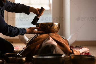 Woman making relaxing massage, meditation, sound therapy with tibetian singing bowls. Stress relief