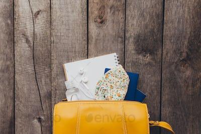 Flat lay travel concept, passport, sanitizer, bag, notepad, wooden background