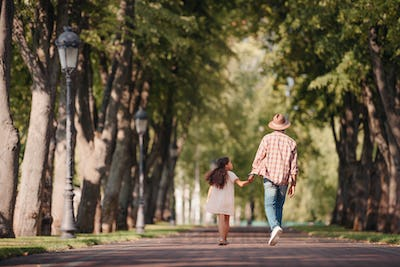 back view of african american girl holding hands with grandfather and walking in park