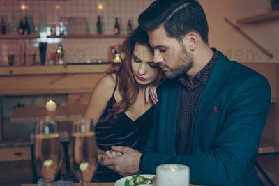 young couple in love having romantic dinner together in restaurant
