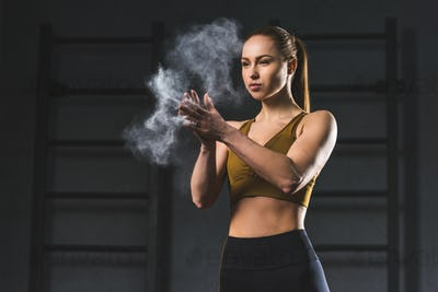 Young sportswoman spreading chalk powder in hands for exercising in sports hall