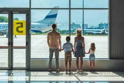 rear view of family looking out window together in airport