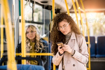 beautiful young woman in eyeglasses using smartphone in public transport