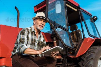 senior farmer in straw hat using digital tablet near red tractor
