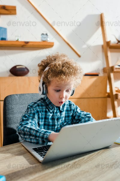 selective focus of surprised kid typing on laptop while listening music in wireless headphones