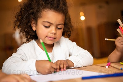 adorable african american kid erasing pencil from sheet of paper in kindergarten