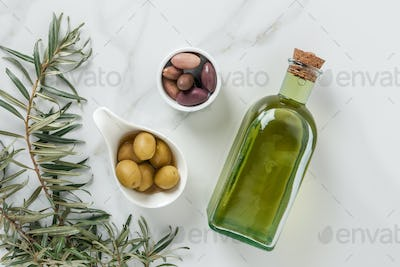 top view of olive oil and yummy olives in bowls on marble surface