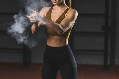 Cropped image of young sportswoman spreading chalk powder in hands for exercising in sports hall