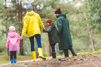 back view of parents and kids holding hands together while walking in autumn forest