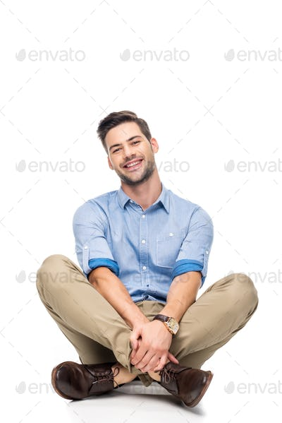 happy young man sitting on floor with crossed legs isolated on white