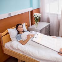 Female patient lying in hospital bed and looking at male doctor with folder
