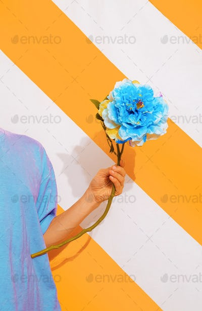 Unrecognizable model on trend striped yellow background with flower  in her hands.