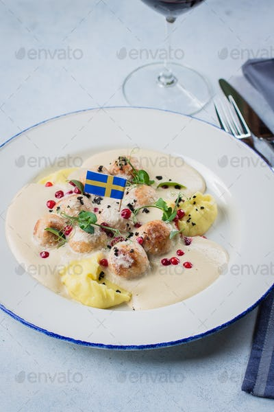 Meatballs with boiled potatoes, sauce and crunberry berry decorated by Swedish flag