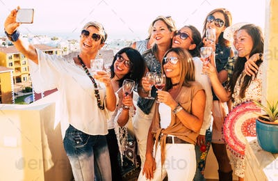 Group of people women enjoying party on the terrace celebrating and toasting with red wineglass