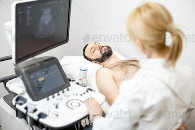 Doctor examining liver of male patient with ultrasound scan in clinic
