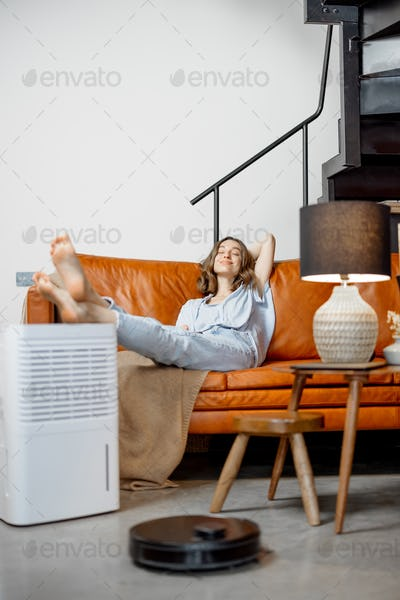 Woman sitting near air purifier and robotic vacuum cleaner