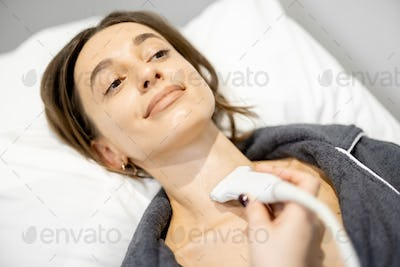 Doctor examining thyroid of female patient with ultrasound scan in clinic