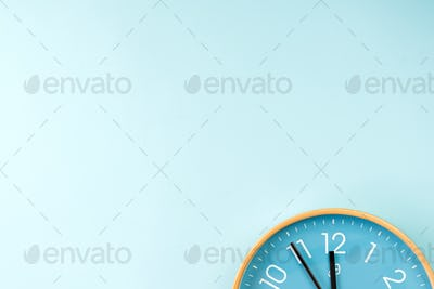 Closeup of colorful wall clock on blue background. Minimalist flat lay image of plastic wall clock .