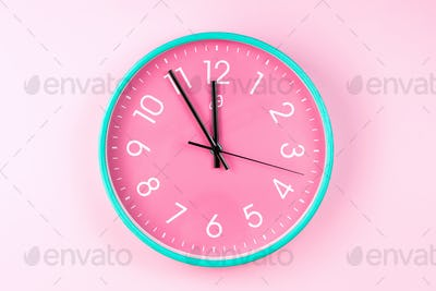 Closeup of colorful wall clock on pink background. Minimalist flat lay image of plastic wall clock .