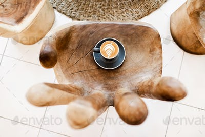Cup of coffee with latte-art on wooden table in hand shape