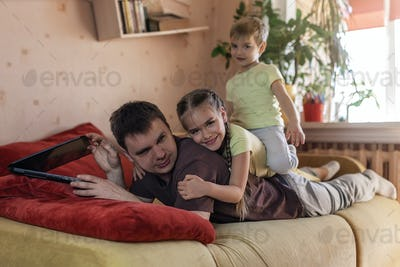 Happy man with children using laptop and earphone during his home working, life in quarantine