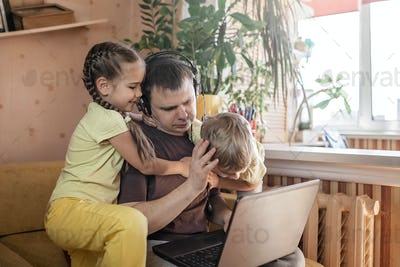 Man with children using laptop and earphone during his home working, life in quarantine