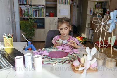 Girl doing flowers with toilet roll tube via online master class, zero waste Easter and Mother Day