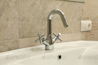 Sink and faucet in modern bathroom, close up