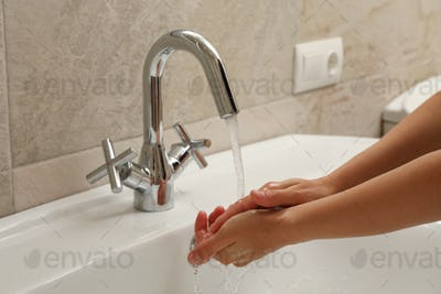 Woman washes her hands in the sink
