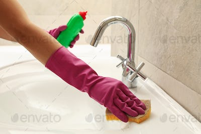 Woman in rubber pink glove cleaning sink