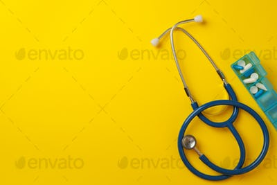 Stethoscope and box with pills on yellow background