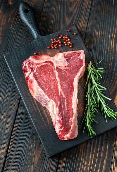 Raw T-bone steak with fresh rosemary