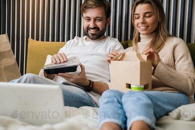 Couple eating take-away food in bedroom