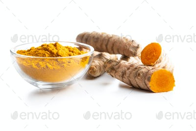 Indian turmeric powder and root. Turmeric spice. Ground turmeric on white background.