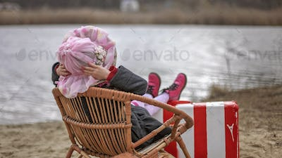Girl in a coat and flowers garland sitting on beach in early spring day and enjoying beautiful view