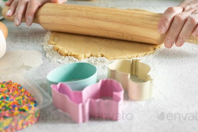 Female model rolls dough with rolling pin on kitchen table