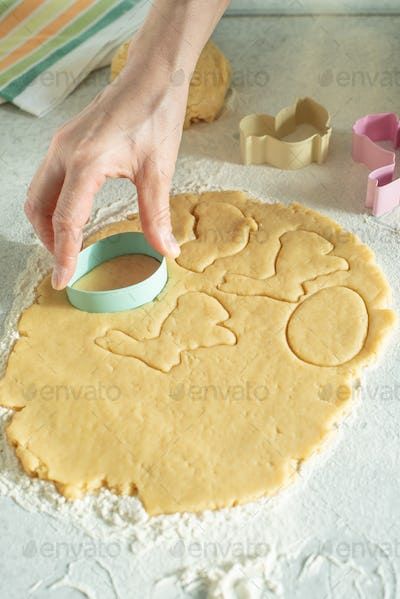 Female model cut dough with cookie cutter on kitchen table