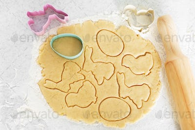 Dough with cookie cutters and rolling pin on kitchen table