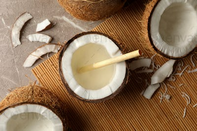 Tasty coconut with straw on bamboo background